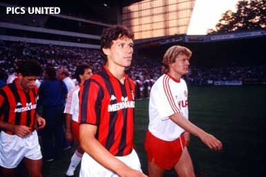 © Pics United - Sören Lerby walks onto the AC Milan pitch, accompanied by Marco van Basten.